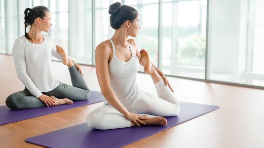 Flexible young woman and her friend making yoga exercise for stretching in gym